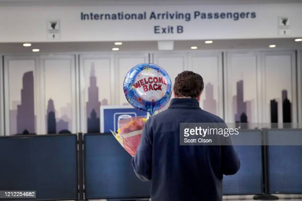 Travelers arrive in the international terminal at O'Hare Airport on March 13 2020 in Chicago Illinois Today was the last day for travelers from 26...