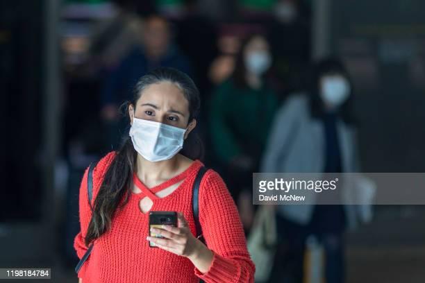 Travelers arrive to LAX Tom Bradley International Terminal wearing medical masks for protection against the novel coronavirus outbreak on February 2...