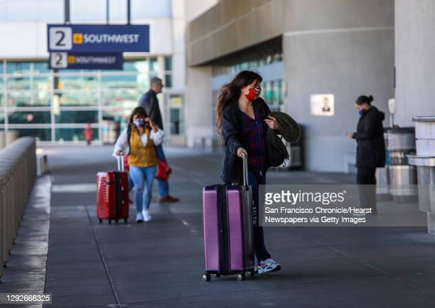 Travelers arrive to Oakland International Airport on Tuesday, December 22 in Oakland, Calif. Many folks are still traveling despite coronavirus...