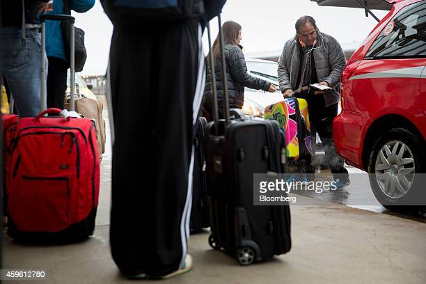 Travelers arrive to Ronald Reagan National Airport in Washington DC US on Wednesday Nov 26 2014 A storm dropping rain and snow on the US East Coast...