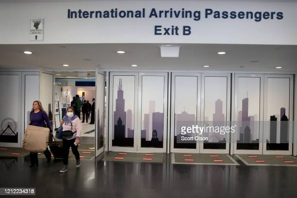 Travelers arrives in the international terminal at O'Hare Airport on March 13 2020 in Chicago Illinois Today was the last day for travelers from 26...