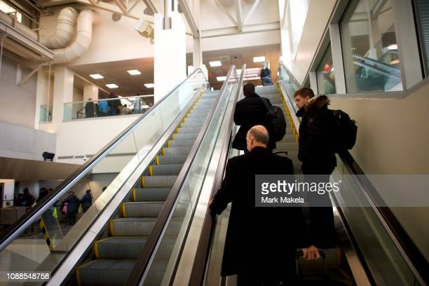 Travelers ascend an escalator to a long security line after Philadelphia Airport TSA and airport workers held a protest rally outside the...