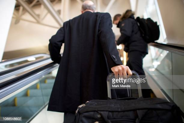 Travelers ascend an escalator to security after Philadelphia Airport TSA and airport workers held a protest rally outside the Philadelphia...