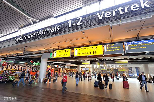 Travelers at departures and arrivals hall of  Amsterdam Airport Schiphol