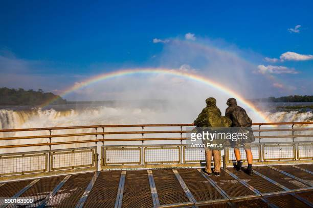 travelers at iguazu falls. view of the rainbow and a waterfall. argentina. - iguacu falls stock pictures, royalty-free photos & images