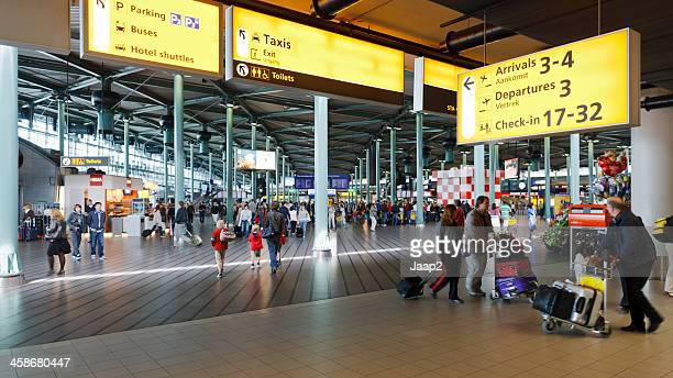 travelers at schiphol airport - schiphol airport stock photos and pictures