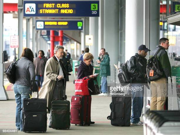 Travelers await curbside luggage checkin outside the American Airlines terminal at O'Hare International Airport in Chicago Illinois US on Wednesday...