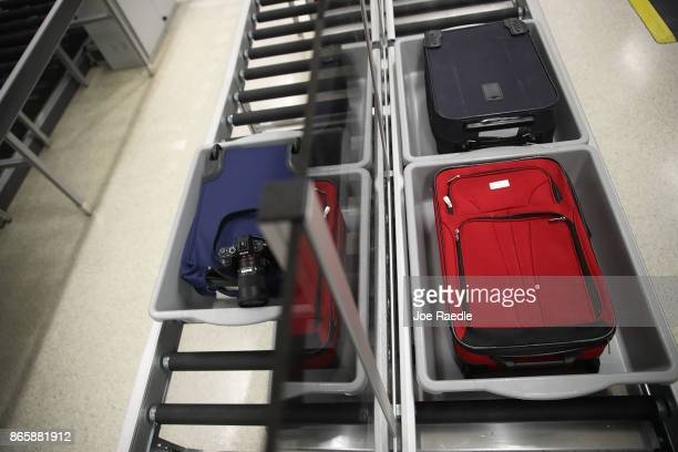 Travelers bags pass through the automated screening lanes funded by American Airlines and installed by the Transportation Security Administration at...