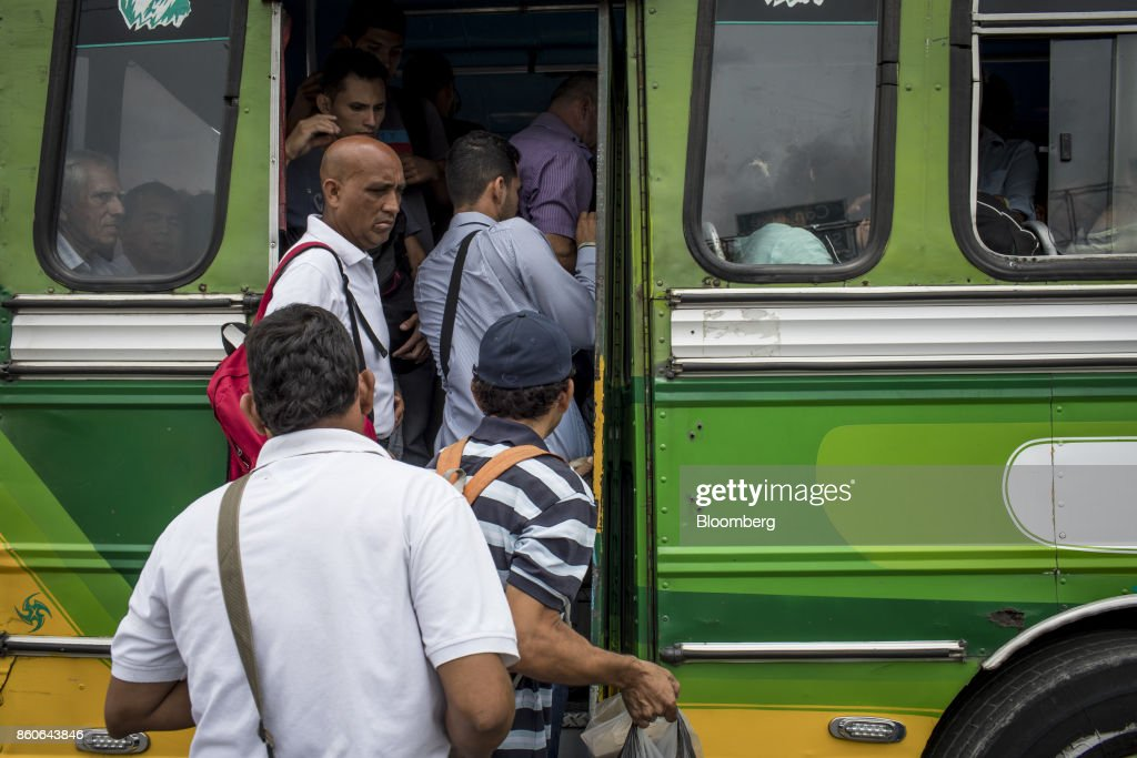 Travelers board a bus at a stop near the San Antonio International Border in Cucuta, Colombia, on Thursday, Sept. 21, 2017. For weeks, Venezuelans have been flocking by the busload to San Antonio del Tachira, a border town of some 62,000 residents, fleeing as President Nicolas Maduro consolidates autocratic power. According to Colombia's migration authority, the number of foreigners entering Cucuta, the first major city across the bridge, more than doubled this summer. Photographer: Nicolo Filippo Rosso/Bloomberg via Getty Images