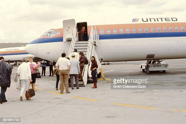 Travelers board a United Airlines jet using boarding stairs 1975