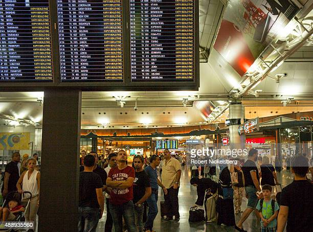 Travelers check an electronic flight board for their time of departure and gate August 29 2015 at the Istanbul Ataturk Airport in Istanbul Turkey