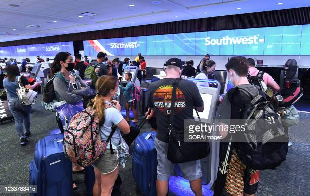 Travelers check in for a Southwest Airlines flight at Orlando International Airport as the July 4th holiday weekend begins. Americans are expected to...