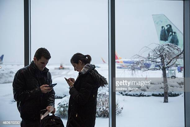 Travelers check their phones while waiting for their flight at La Guardia Airport during a winter storm on February 2 2015 in the Queens borough of...