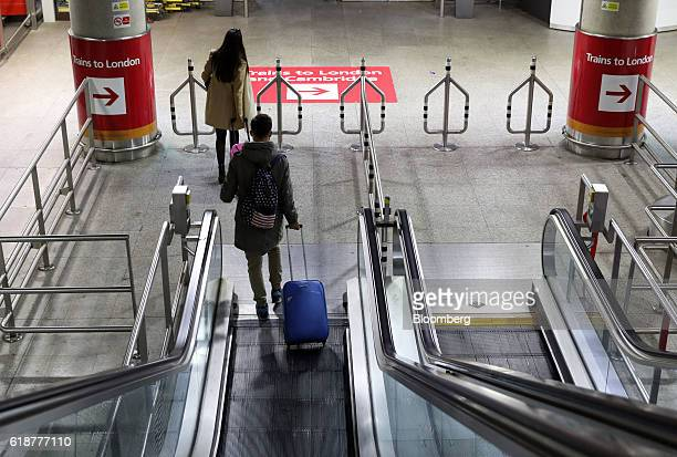 Travelers descend an escalator towards the Stansted Express train service to London from London Stansted Airport operated by Manchester Airports...