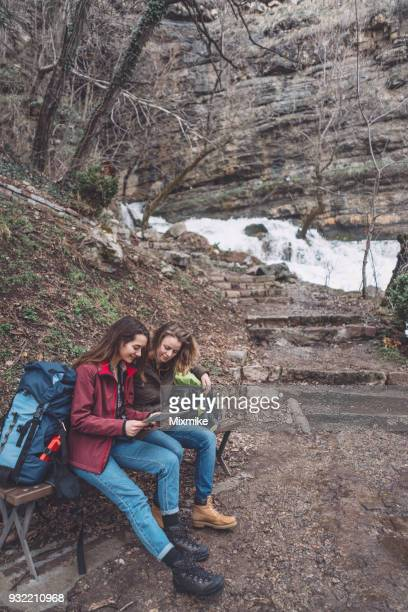 Travelers discussing the hiking route while sitting near small waterfall