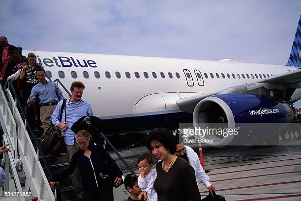 Travelers disembark a JetBlue flight at Long Beach Airport