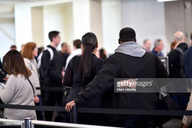 Travelers embrace while waiting in a long security line after Philadelphia Airport TSA and airport workers held a protest rally outside the...