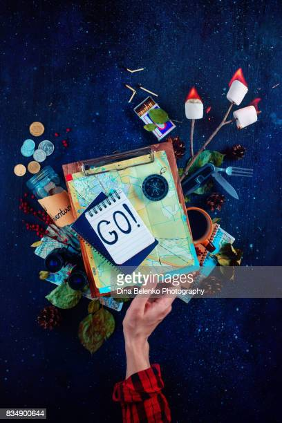 Travelers essentials (maps, compass, notes) with roasted marshmallows and open flame on a dark background. Woman hand holding a tablet with maps of routes.