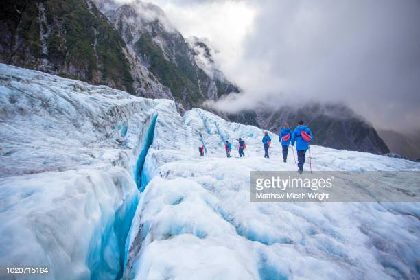 Travelers explore New Zealand's famous Franz Josef Glacier. Blue Ice, deep crevasses, caves and tunnels mark the ever changing ice.