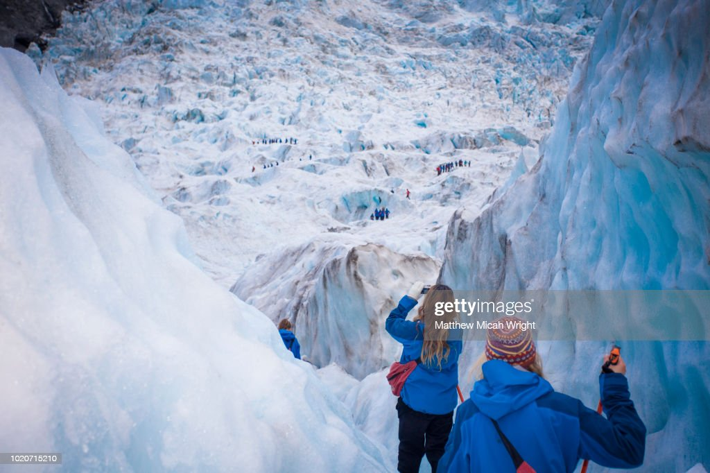 Travelers explore New Zealand's famous Franz Josef Glacier. Blue Ice, deep crevasses, caves and tunnels mark the ever changing ice. : Stock Photo