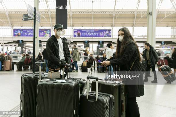 Travelers from Milan wear face masks as they stand with their luggage after arriving at Paris at Gare de Lyon railway station in Paris France on...