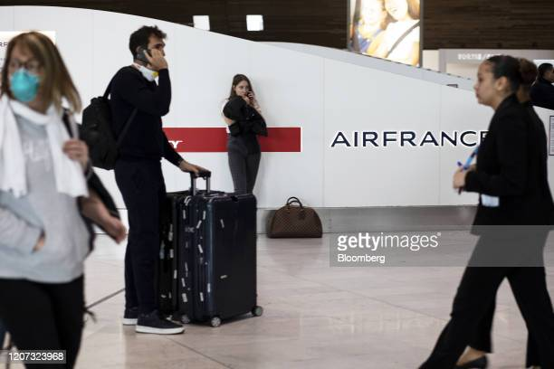 Travelers gather near the Air FranceKLM ticket office at Charles de Gaulle Airport operated by Aeroports de Paris in Roissy France on Monday March 16...
