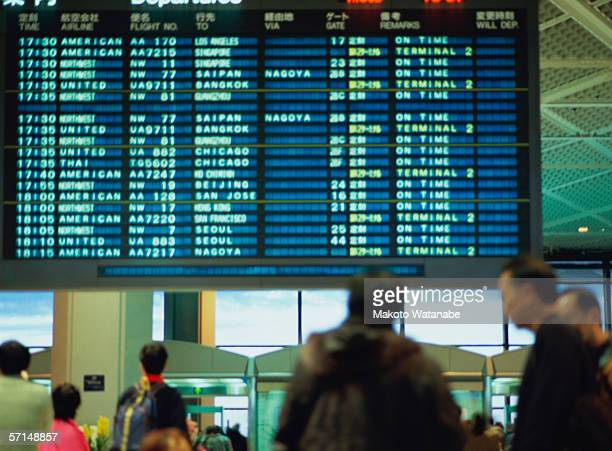 Travelers in front of arrival departure board at airport terminal