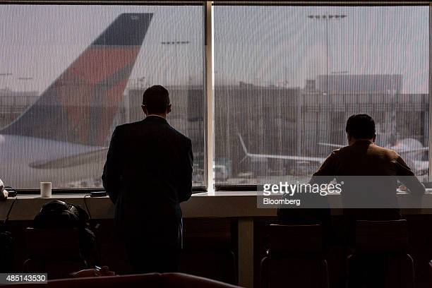 Travelers look out at the tarmac from the Delta Air Lines Inc Sky Club in Terminal 5 at Los Angeles International Airport in Los Angeles California...