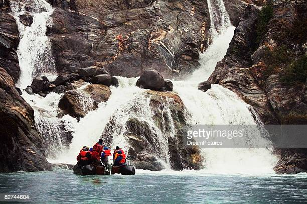 travelers looking at waterfall in le conte bay - eco tourism stock pictures, royalty-free photos & images