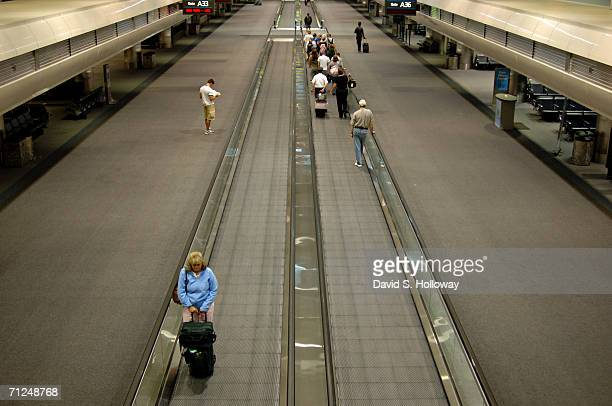Travelers make their way along a people mover in the Jeppesen Terminal, named after aviation pioneer Elrey B. Jeppesen as seen at Denver...