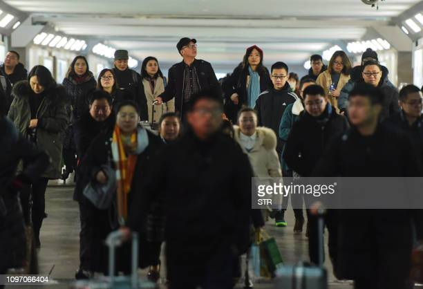 Travelers make their way through an alley at a railway station in Hangzhou in China's eastern Zhejiang province on the last day of the Spring...