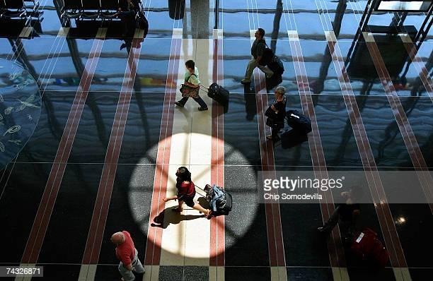 Travelers move through Ronald Reagan Washington National Airport May 25 2007 in Arlington Virginia According to AAA MidAtlantic about 60000...