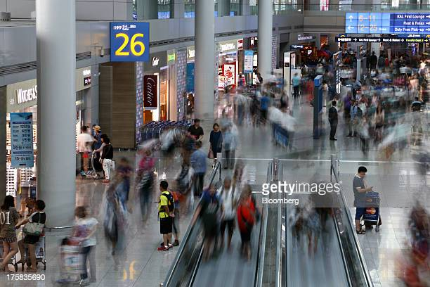 Travelers move through the duty free shopping area in this long exposure photograph taken at Incheon International Airport in Incheon South Korea on...