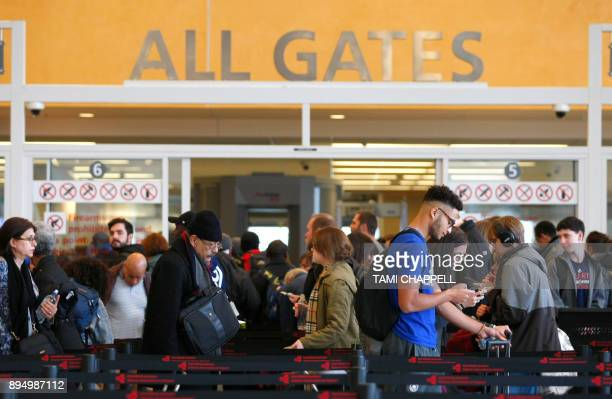 Travelers move through waiting lines at the international counter the day following a major power outage caused by a fire at HartsfieldJackson...
