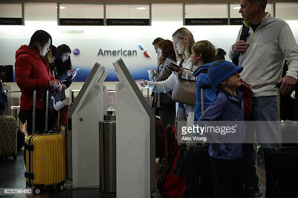Travelers obtain boarding passes from kiosks as they check themselves in at Ronald Reagan Washington National Airport November 23 2016 in Arlington...