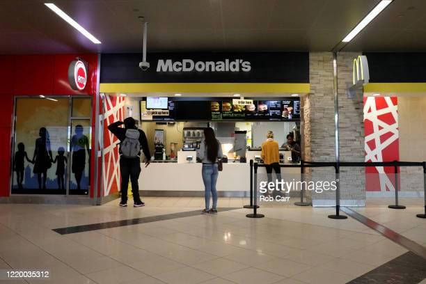 Travelers order food from McDonald's at HartsfieldJackson Atlanta International Airport on April 20 2020 in Atlanta Georgia The airline industry has...