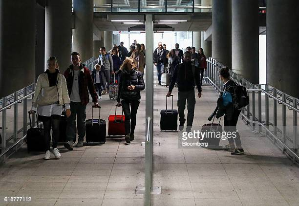 Travelers pass along a walkway towards the Stansted Express train service to London at from London Stansted Airport operated by Manchester Airports...