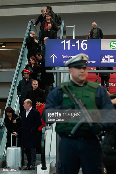 Travelers pass by a German policeman armed with a submachine gun at Hauptbahnhof main railway station on November 17 2010 in Berlin Germany Germany's...