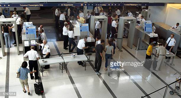 Travelers pass through a security checkpoint manned with new Transportation Security Agency employees in Terminal 5/International Departures at...