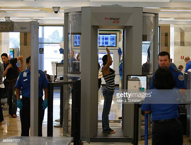 Travelers pass through security including a new body scanner shown at right atJohn Wayne Airport's new Terminal C Five new security screening lanes...