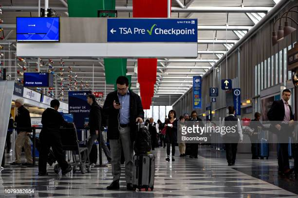 Travelers pass under a sign pointing toward a Transportation Security Administration PreCheck checkpoint at O'Hare International Airport in Chicago...