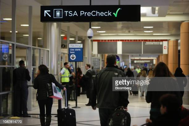Travelers pass under a sign pointing toward a Transportation Security Administration PreCheck checkpoint at HartsfieldJackson Atlanta International...