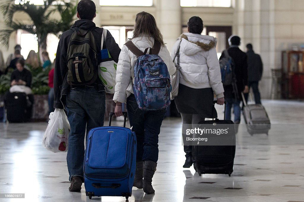Travelers pull luggage while walking out of Union Station in Washington, D.C., U.S., on Wednesday, Nov. 21, 2012. U.S. travel during the Thanksgiving holiday weekend will rise a fourth straight year, gaining 0.7 percent from 2011, as trips by automobile rise even as airplane trips decline, AAA said last week. Photographer: Andrew Harrer/Bloomberg