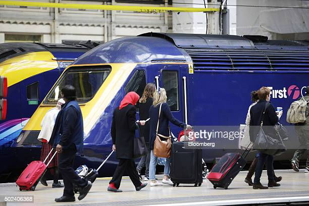 Travelers pull their luggage along a platform as passenger trains operated by First Great Western stand at Paddington railway station in London UK on...