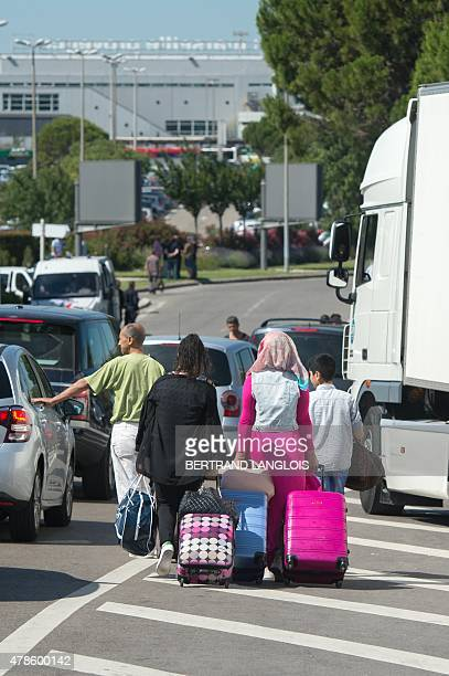 Travelers pull their luggage past striking taxi drivers blocking the access of the airport of Marignane near Marseille, southern France, on June 26,...