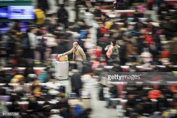 Travelers push their luggage through the main hall of the Shanghai Hongqiao Railway Station in Shanghai China on Monday Feb 12 2018 Almost 400...