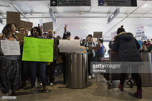 A travelers pushes luggage as demonstrators gather holding signs inside Los Angeles International Airport protesting US President Donald Trump's...