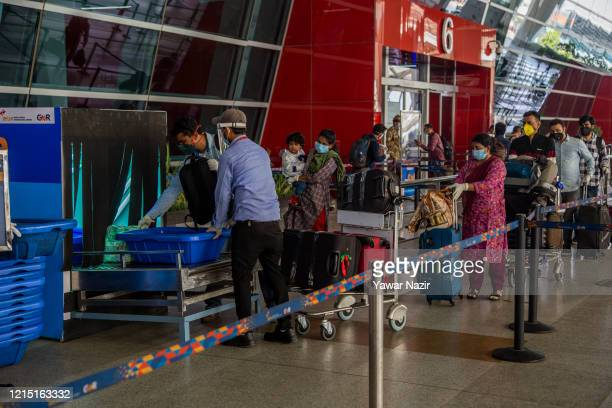 Travelers put their luggage in Xray machine before at the dropoff point before entering Terminal 3 of the Indira Gandhi International Airport as the...