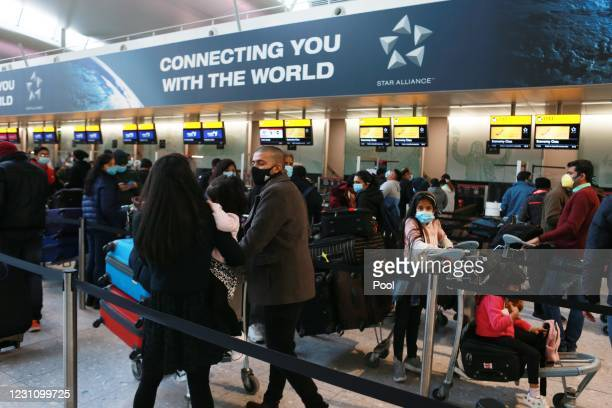 Travelers queue to check in at Terminal 2 at Heathrow Airport on February 11, 2021 in London, England.