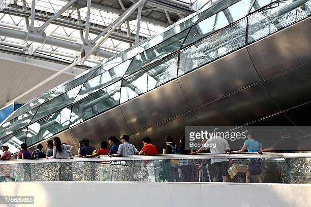 Travelers ride an escalator at Incheon International Airport in Incheon South Korea on Thursday Aug 8 2013 South Korea plans to tighten aviation...